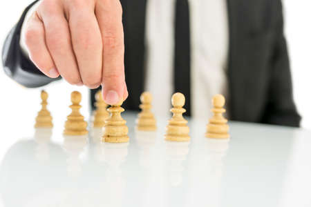 Closeup of businessman arranging chess figures pawns. Concept of human resources. photo