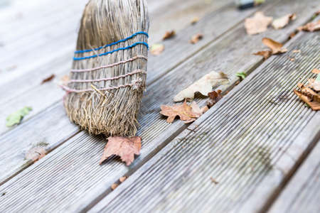 porch: Closeup of sweeping autumn leaves off a wooden porch.