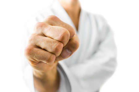 Closeup of male karate fighter making a fist. Isolated over white background. photo