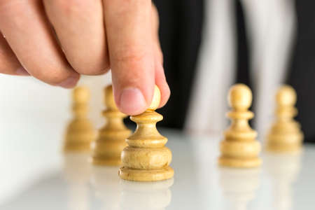 Closeup of businessman moving pawn chess figure. Leadership concept. photo