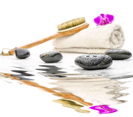 Spa setting with massage stones, brush and towel next to tranquill water. photo