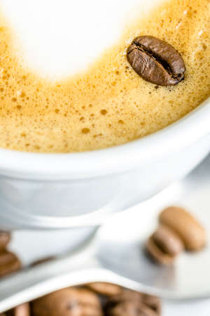 Closeup of coffee bean on cafe latte milk foam. photo