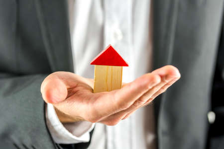 developing: Closeup of real estate agent holding a wooden  house in his hand. Real estate business.  Stock Photo