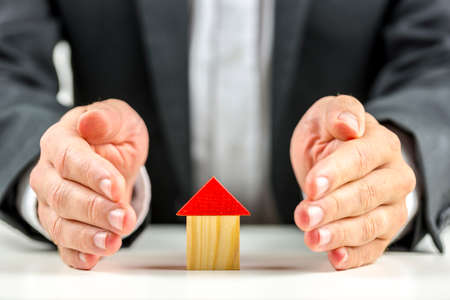 financial security: Male hands giving energy to a wooden toy house. Concept of solution to real estate market crisis.