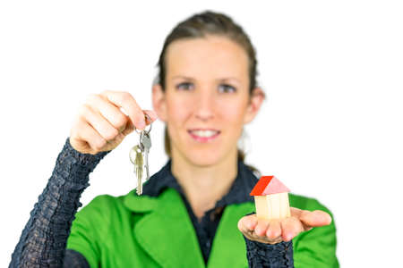 Female real estate agent holding house keys in one and wooden toy house in the other hand. Isolated over white background. photo