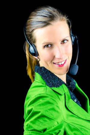 Portrait of young female call center employee. Isolated over black background. photo