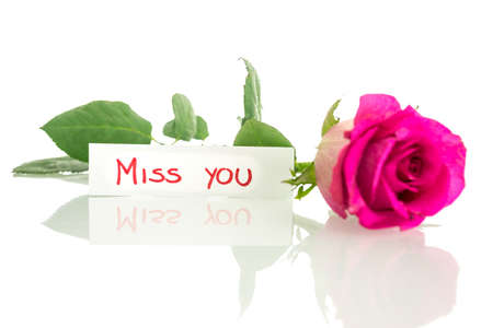 Beautiful pink rose lying on a desk with a Miss you card. Over white background.