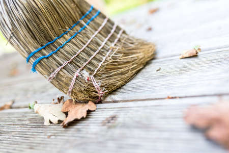 Closeup of sweeping autumn leaves off wooden patio with a broom.