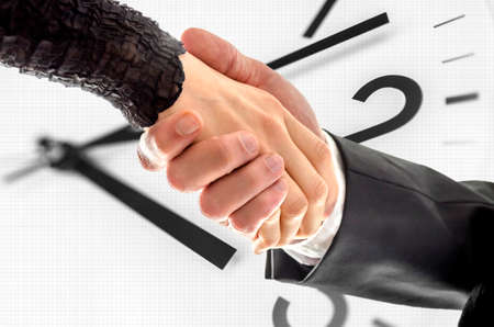 Man and woman business handshake with white clock in background.