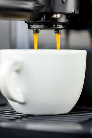 Coffee machine pouring espresso into a cup. photo