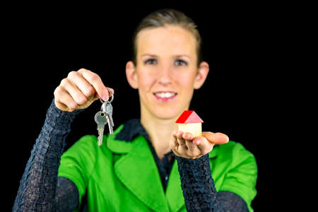 Young female real estate agent holding wooden toy house in one and keys in other hand. Isolated over black background. photo