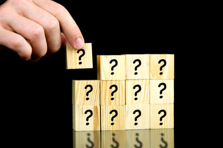 unknowing: Male hand placing last piece of a cube with question mark  Stock Photo