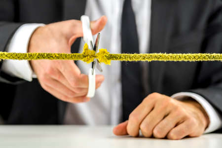 Businessman cutting yellow rope. Bad business or ending career concept. Фото со стока - 23337220