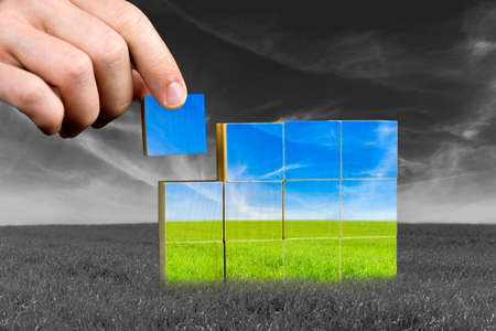 optimism: Male hand placing last piece of a cube of color grass field. Ecological or positive concept.