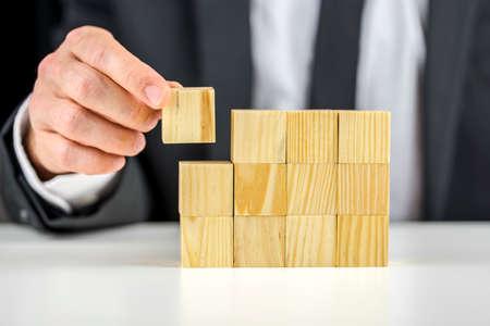 木製キューブの構造を作るビジネスマンのクローズ アップ。ビジネス コンセプトを構築しています。