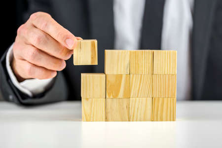 Closeup of businessman making a structure with wooden cubes. Building a business concept. Stock Photo