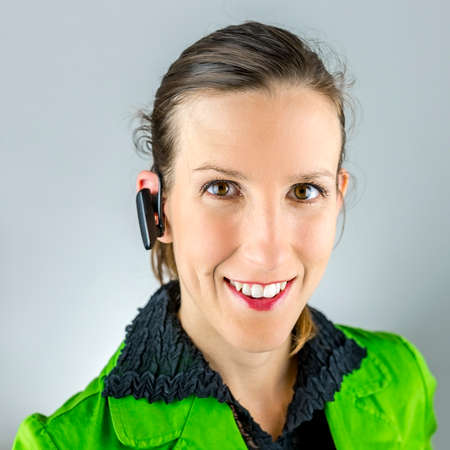 Portrait of young female call center agent with wireless headset. Stock Photo - 23529206