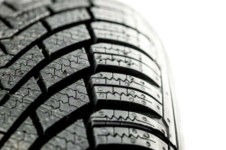 vulcanization: Closeup of new winter tire. Isolated over white background.