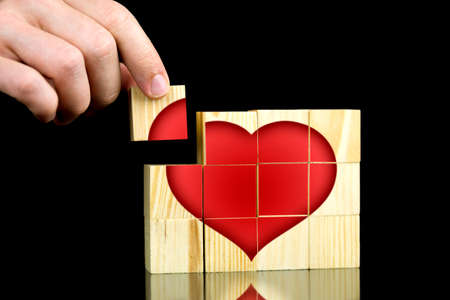 Male hand putting together pieces of heart shape on a wooden cubes. Isolated over black .  photo