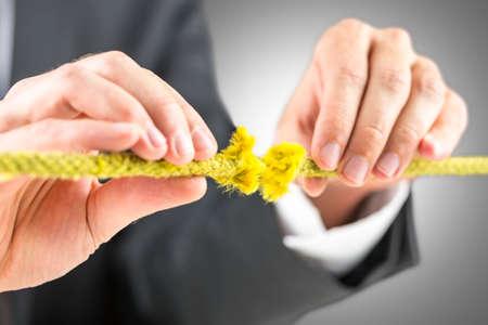 결함이있는 노란색 밧줄을 잡고 남성 손의보기를 잘립니다. 스톡 콘텐츠 - 23678794