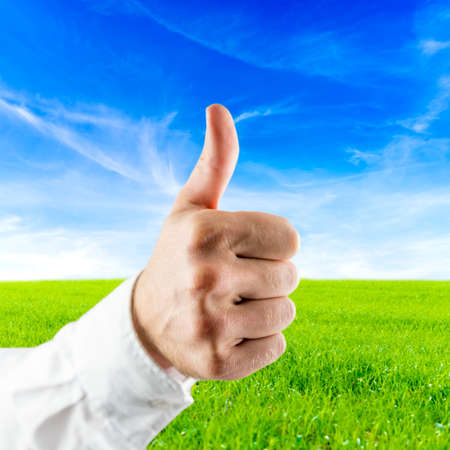 Closeup of male hand showing thumbs up sign with beautiful nature . Stock Photo - 23678811