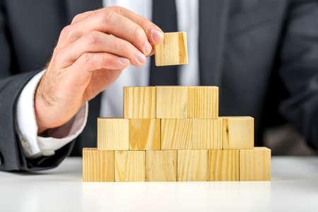 Close-up van zakenman maken van een piramide met lege houten kubussen. Concept zaken hiërarchie en human resources. Stockfoto
