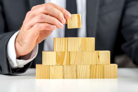 Closeup of businessman making a pyramid with empty wooden cubes. Concept of business hierarchy and human resources.