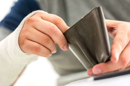 reimbursement: Closeup of male hand in plaster holding an open wallet  Concept of indemnification  Stock Photo