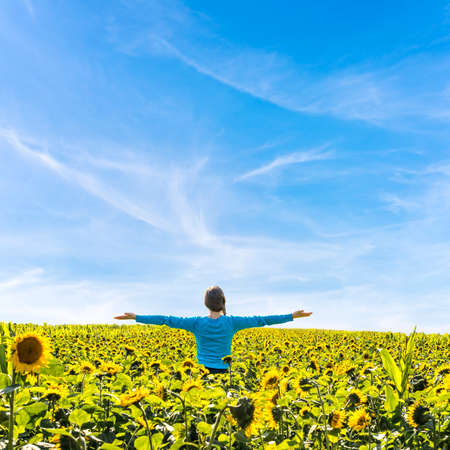 Woman with her arms wide open standing in beautiful field of blooming sunflowers  photo