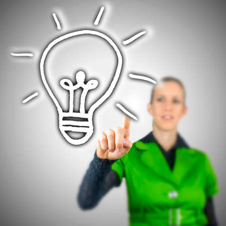 originality: Young woman choosing light bulb icon on virtual screen.