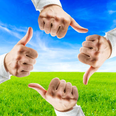Save the planet concept. Four hands showing thumbs up sign over beautiful nature in background. Stock Photo - 24050782