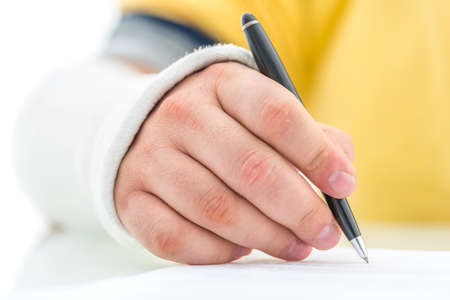 recompense: Closeup of injured male hand in plaster signing insurance policy.