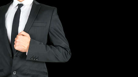 tailored: Front view of businessman torso in elegant business suit. Isolated over black background. Empty space ready for your text.