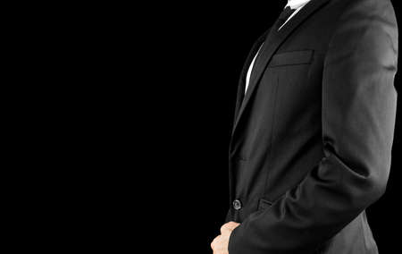 tailored: Side view of businessman torso in elegant suit. Isolated over black background. Empty space ready for your text. Stock Photo
