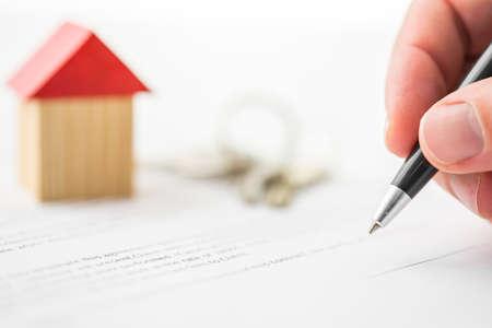 Close-up van de ondertekening van het contract van verkoop huis.