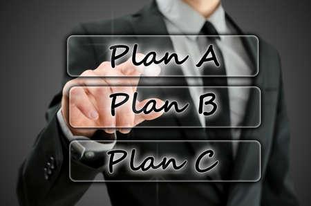 adapting: Businessman choosing Plan A on virtual screen. Stock Photo