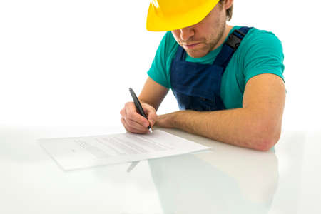 Young construction worker signing contract on white desk. Over white background.