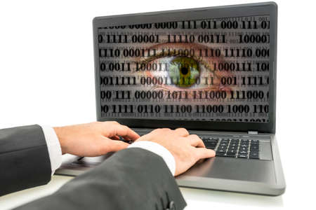 private information: Hacker working on laptop with human eye with digital binary code on screen. Concept of internet surveillance and espionage.