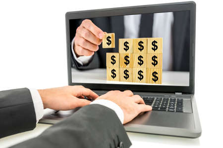 earn money online: Businessman using laptop with structure on wooden cubes with dollar sign on monitor screen. Concept of online earnings. Stock Photo