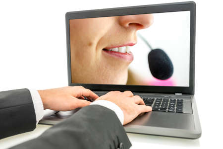 technical support: Closeup of male hands typing on laptop keyboard with female customer service representative on its screen. Stock Photo