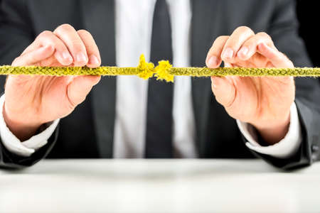 Closeup of business man holding defective rope. Business risk concept.