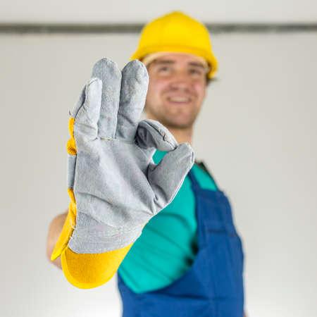 [Ok] 手話を示す若い建設労働者のクローズ アップ