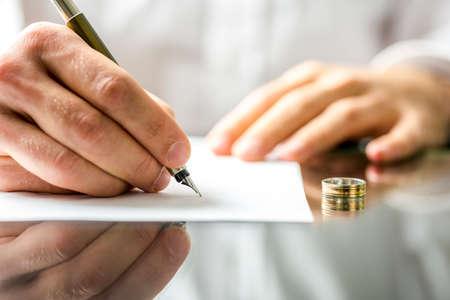 divorcio: Primer plano de un hombre que firma los papeles del divorcio.