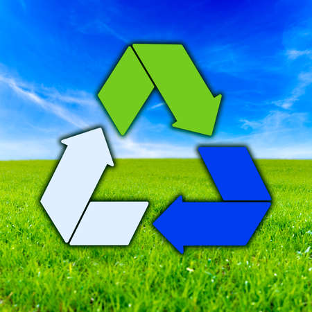 Recycle symbol on beautiful meadow and blue sky.