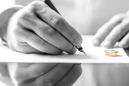 broken contract: Closeup of male hand signing divorce papers. Stock Photo