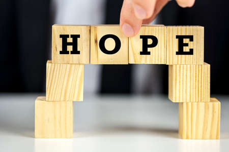 better chances: Building a bridge of wooden cubes with word hope written on them. Inspiration concept.