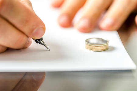 Close-up van mannelijke hand het ondertekenen scheidingspapieren. Stockfoto