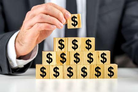 recursos financieros: Primer plano de negocios haciendo una pirámide de cubos de madera con el signo de dólar en ellos. Concepto de la planificación financiera.