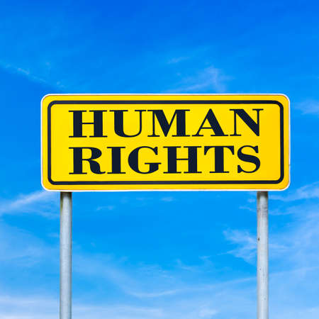 Human rights written on yellow road sign over blue sky. photo
