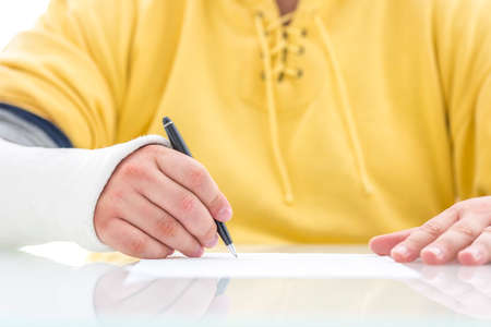 recompense: Closeup of injured male hand in a cast signing insurance policy claim. Stock Photo